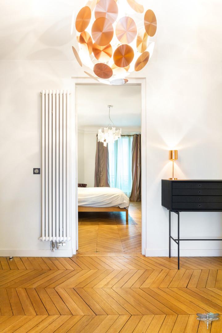 Décoration d'un double salon moderne dans un appartement Haussmannien à Paris 17 par Carnets Libellule. Coralie Vasseur est votre Décoratrice d'intérieur UFDI à Compiegne : vaste entrée en parquet à l'ancienne et vue sur la chambre parentale