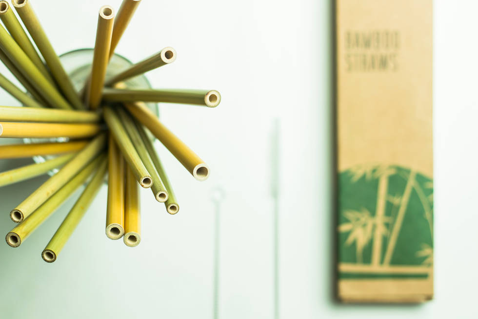 bamboo straws in a glass along with pack