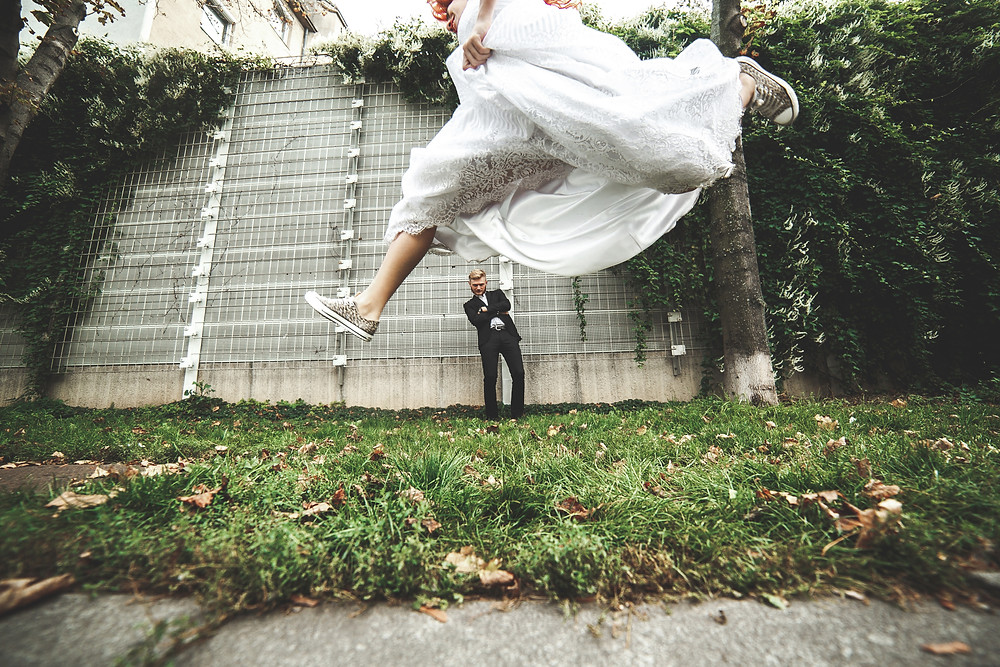 Bride jumping on wedding day, Groom excited.