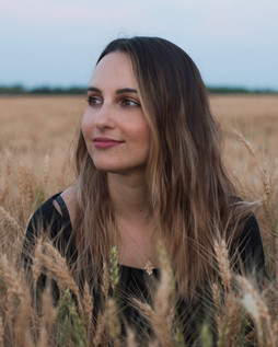 A girl sitting in a golden field looking away