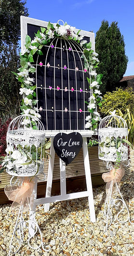 Birdcage design photo display board on a white easel. The frame is decorated with flowers & lights and a large slate heart reading 'Our Love Story' is attached