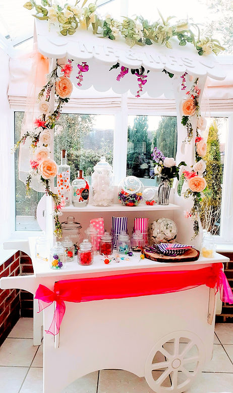 White-washed wooden Sweet Candy Cart, fully stocked with sweets and decorated with floral garlands and bunting.