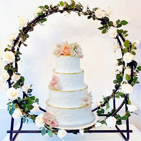 Large floral hoop cake stand, decorated with cream roses, holding a four tier wedding cake