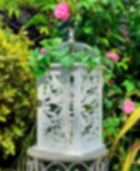 Large white wood lantern with bird & vine cut-out design. The silver top is decorated with ivy & roses.
