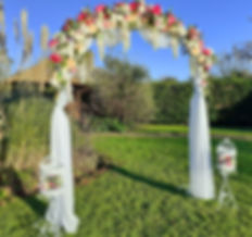 Floral wedding arch dressed with pink, apricot & cream roses, wisteria garlands & chiffon drapes