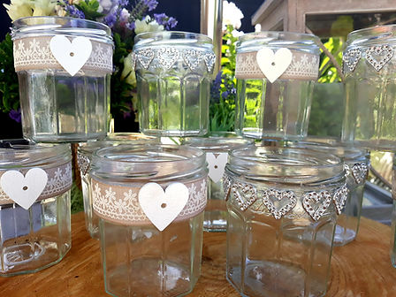 Individually decorated glass jars with hearts, ribbons and rustic decorations