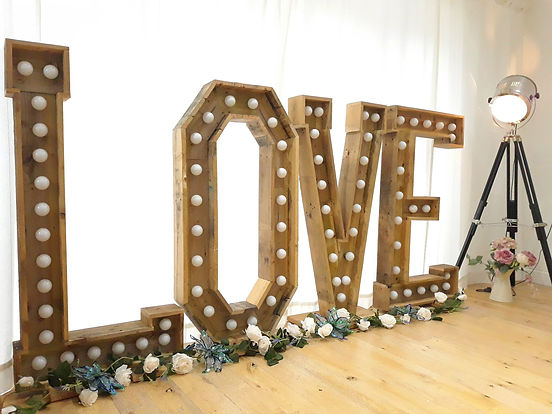 Rustic wooden 4ft. light-up LOVE letters, with cream rose garlands at the base of the letters