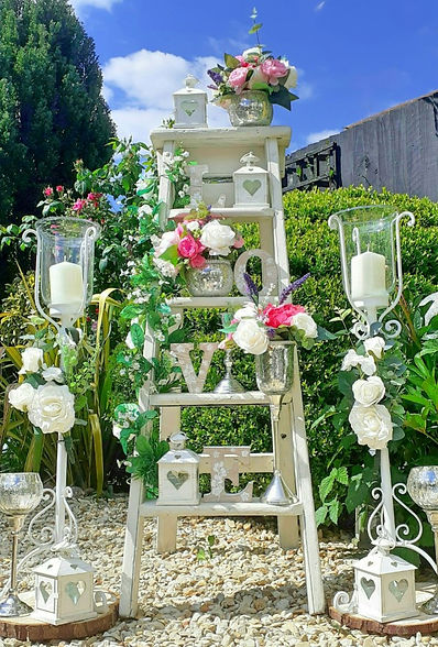 White wooden ladder decorated with wedding accessories including LOVE letters, mini-lanterns, flowers & silverware.