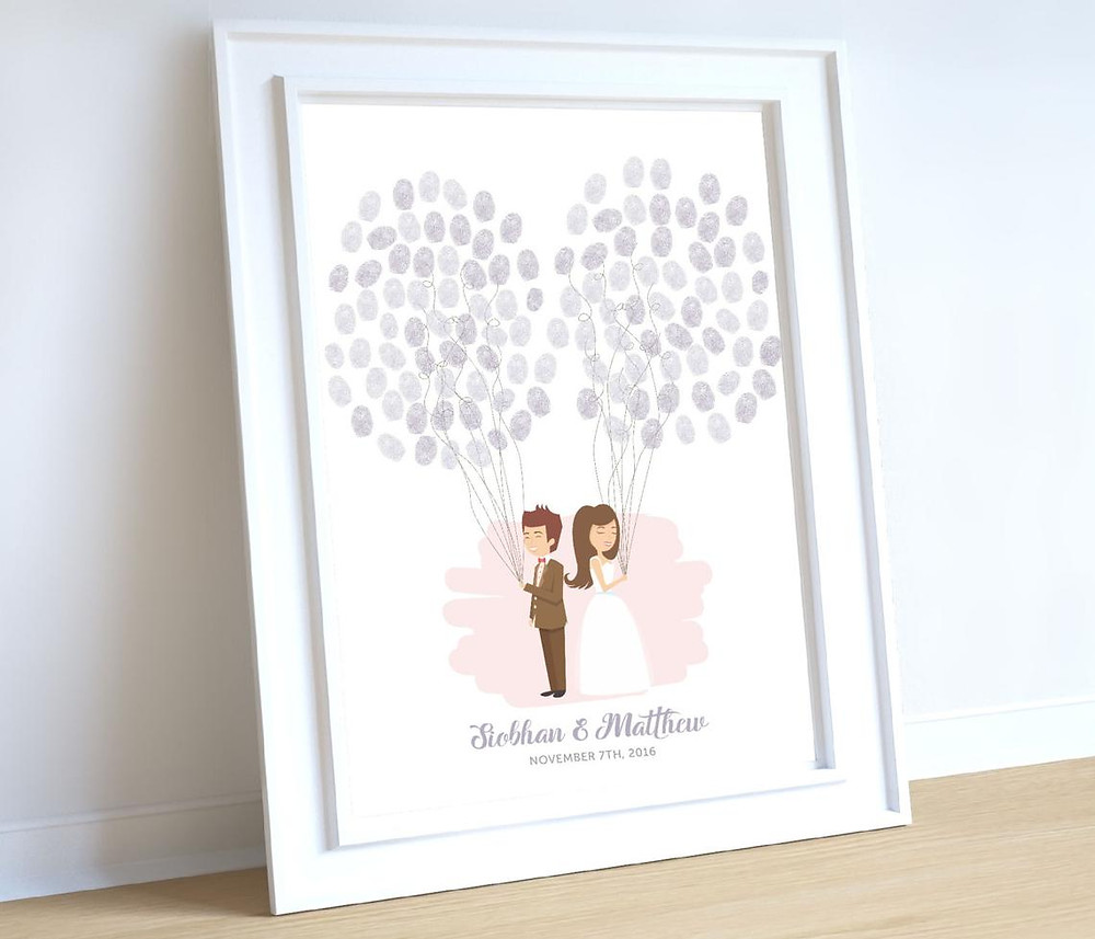 A framed print of a bride & groom holding balloons made of thumbprints by wedding guests