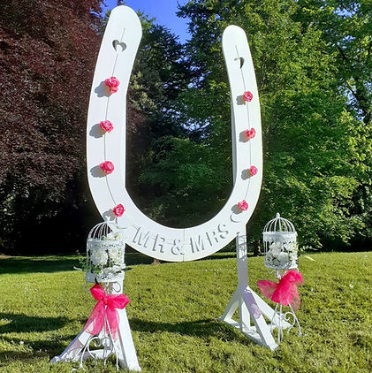 Large freestanding white 'Good Luck' horseshoe shaped photo selfie frame, decorated with roses & ribbons