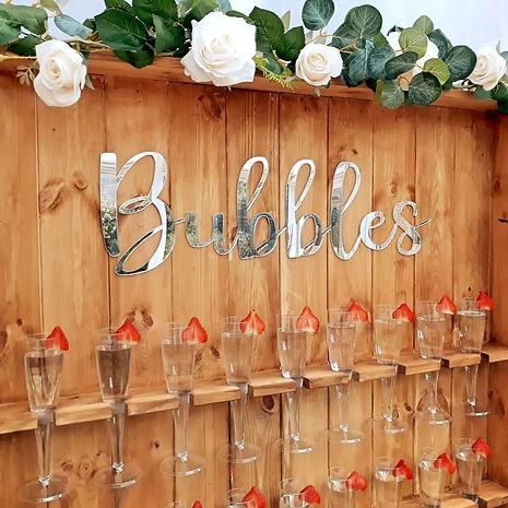 Rustic 'Bubble' Prosecco Wall with champagne glasses