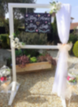 Large free-standing landscape selfie frame decorated with floral garlands and chiffon drapes