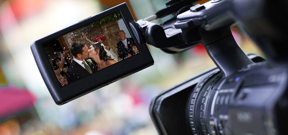 A wedding videographer filming a ceremony