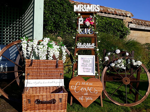Rustic wedding props scene including decorated ladders, confetti hamper & floral cartwheels