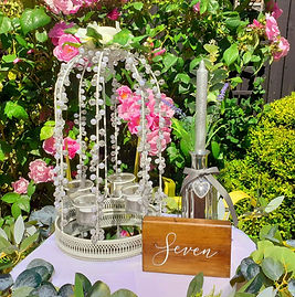A table centrepiece scene with silver mercury glass bottle, floral crystal lantern & rustic oak table number