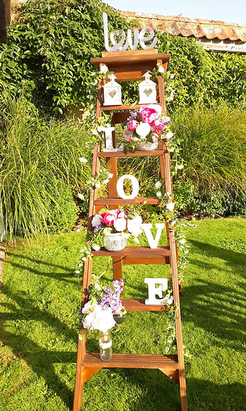 Large oak ladder decorated with wedding accessories including LOVE letters, mini-lanterns, flowers & silverware
