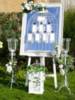 Floral mirror seating plan in a birdcage design, on a white easel. Table cards are attached to the birdcage with chalkboard heart clips
