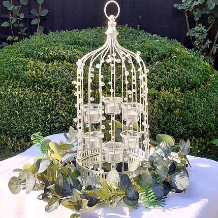 Crystal & pearl birdcage lantern on a large mirror plate, decorated with eucalyptus