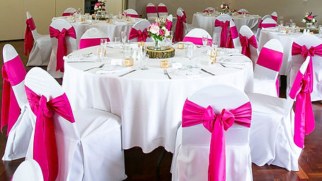 Wedding guest tables dressed with pink chair sashes and pink & cream floral centrepieces