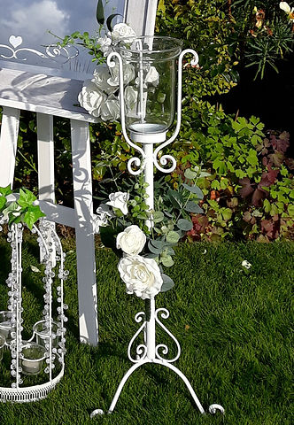 Pedestal white metal scroll & glass pillar candle holders, decorated with white roses