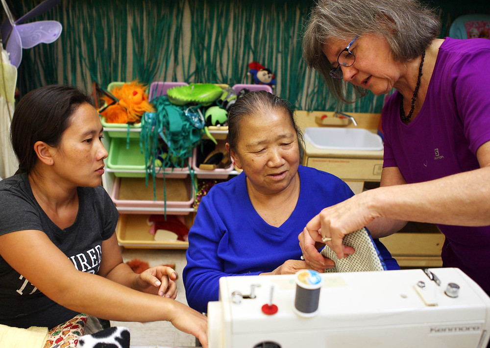 Two students get help sewing from a volunteer