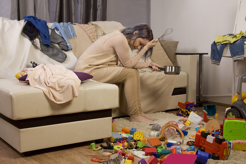 Stressed Mom Sitting on couch surrounded by mess
