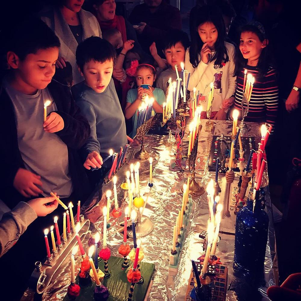 Families light menorahs at a Chanukah party with Amherst Neighborhood Captain, Lili