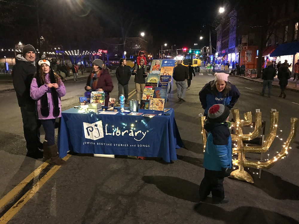 PJ Library pros greeting community members at the PJ Library table during the Holiday Stroll in downtown Northampton