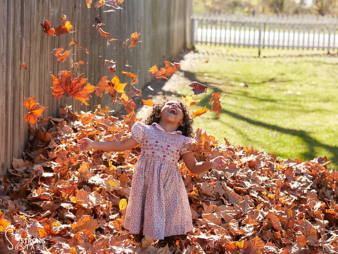 Girl playing in leaves.png