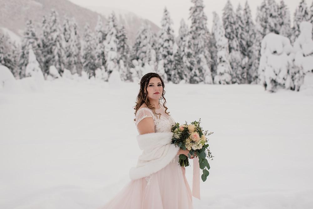 Snowy, winter Alaska elopement. Blush wedding dress in snow