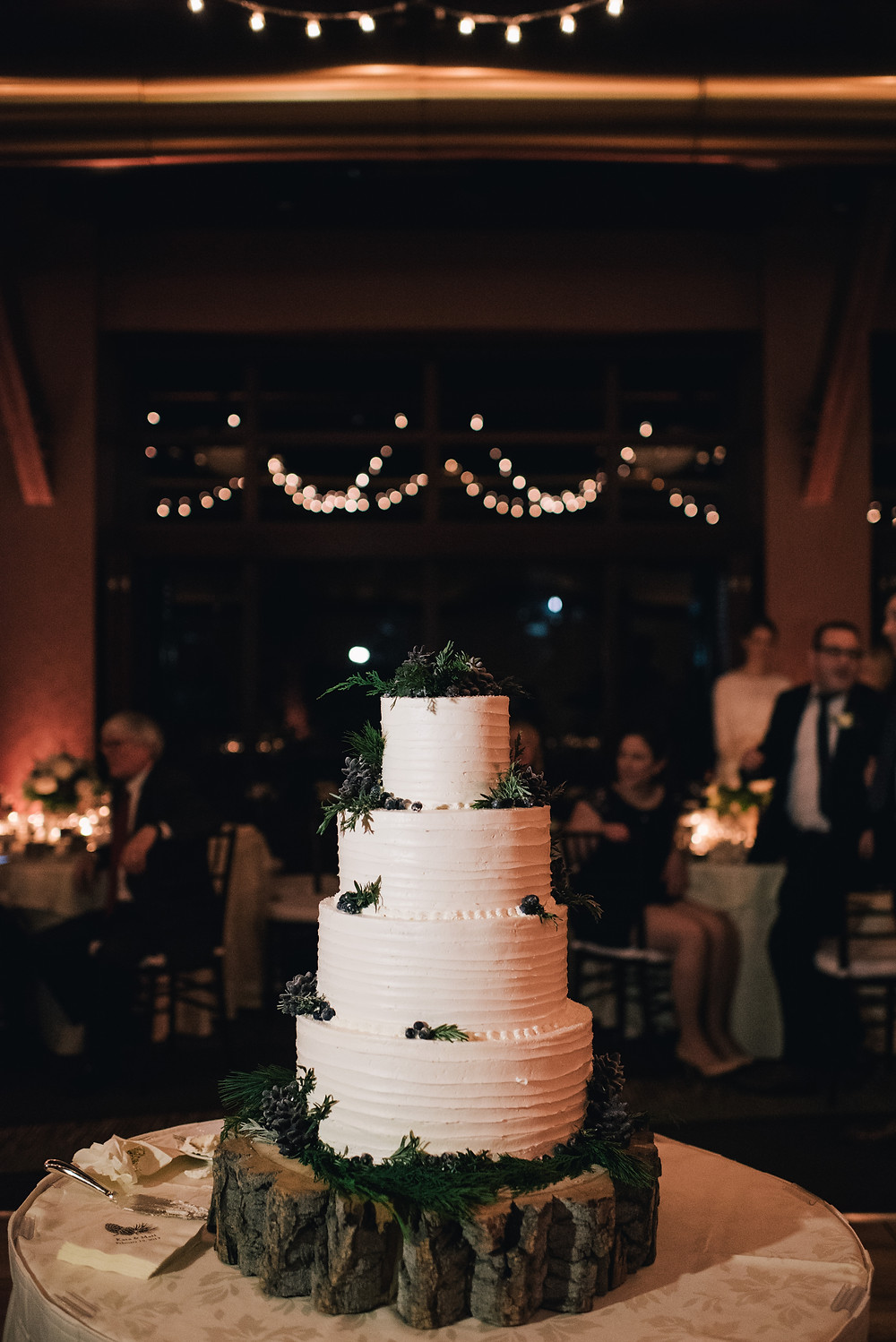 Winter wedding cake with greenery and pinecones