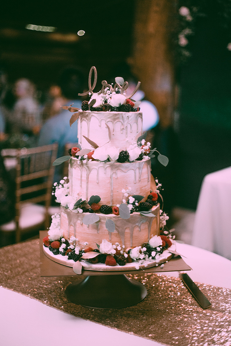 wedding cake with gold drips, berries and Love scrolling topper