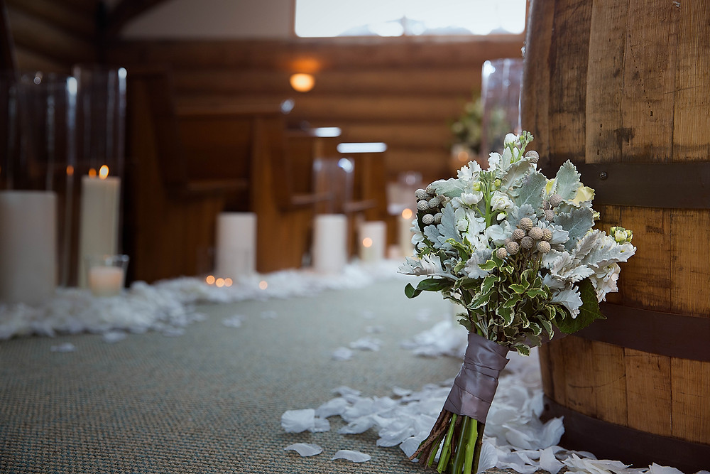 white and silver wedding flowers set in log chapel