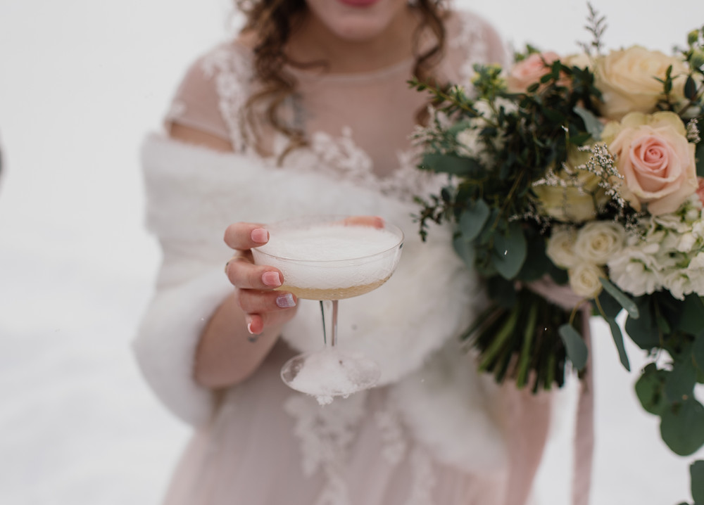 Snowy winter Alaska elopement, with vintage toasting glasses