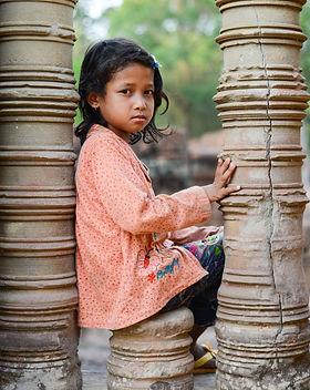 Angkor wat girl sitting on a stone pilla