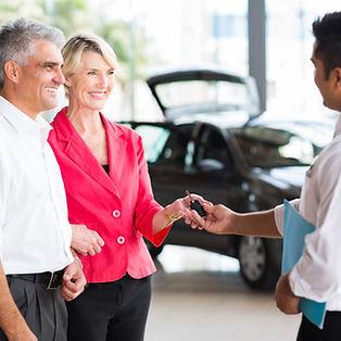 senior couple receiving car key after bu