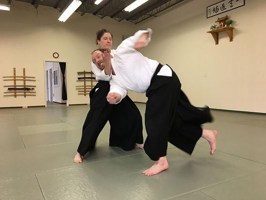 Two studes pratice an Aikijutsu (aikido) martial arts technique in the dojo