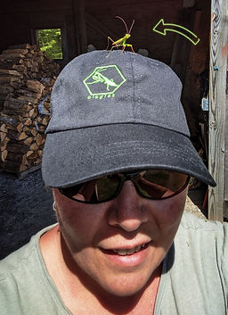Artist headshot outdoors wearing a black Ologies baseball cap with a praying mantis on her head
