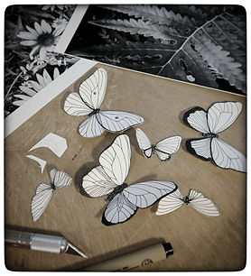 Art in process image of paper butterflies and studio materials