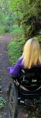 Woman in a wheelchair, wearing purple with blonde hair sitting in the middle of a narrow trail in a very lush forested area.