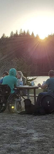 Group of people in wheelchairs sitting around park table that looks out over a lake surrounded by trees while the sunsets in the camera.