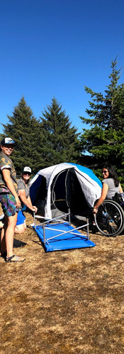 Three women smiling while setting up tent and cot, one of the women in a wheelchair learning how. Full green trees and blue sky in the background.