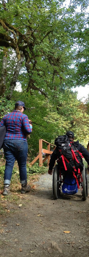 Two women, one in a wheelchair with big backpack on heading towards walking bridge on a trail through big leafy trees.