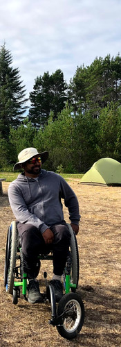 Two men in wheelchairs hanging out in a campground with tents and trees in background.
