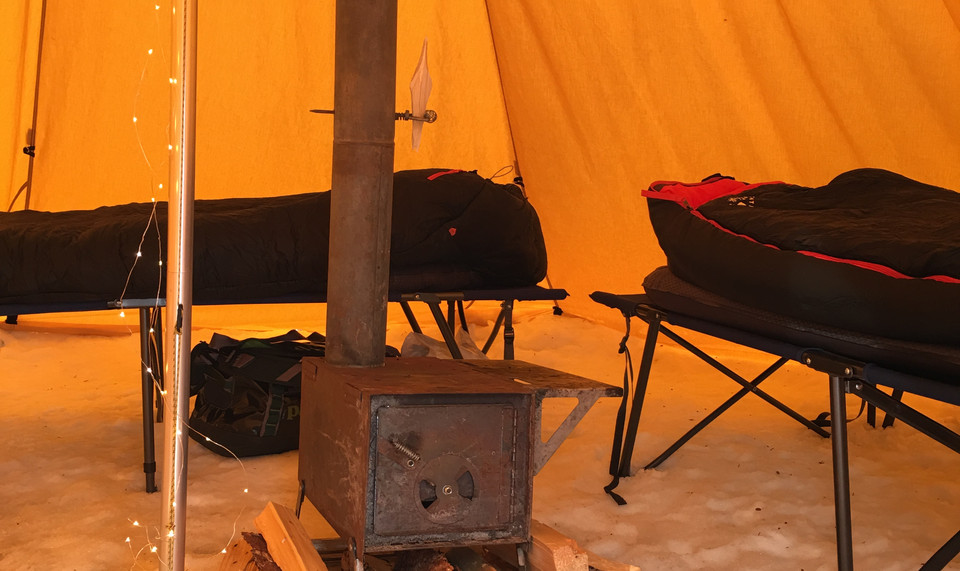 Tipi set up with cots, pads, & a cozy wood stove.