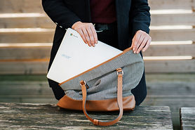 Headless woman putting laptop in bag.jpg
