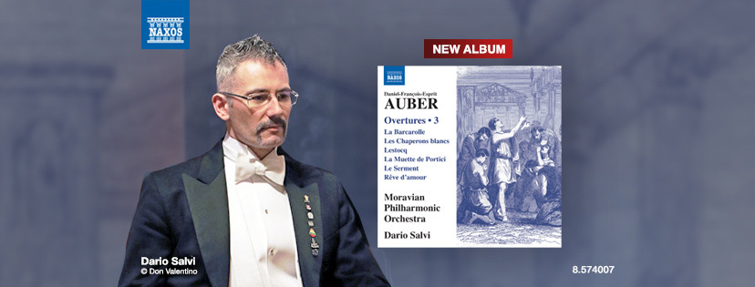 Dario Salvi wearing a tailcoat, white shirt and bow tie next to the album cover of Auber Overtures Volume 3
