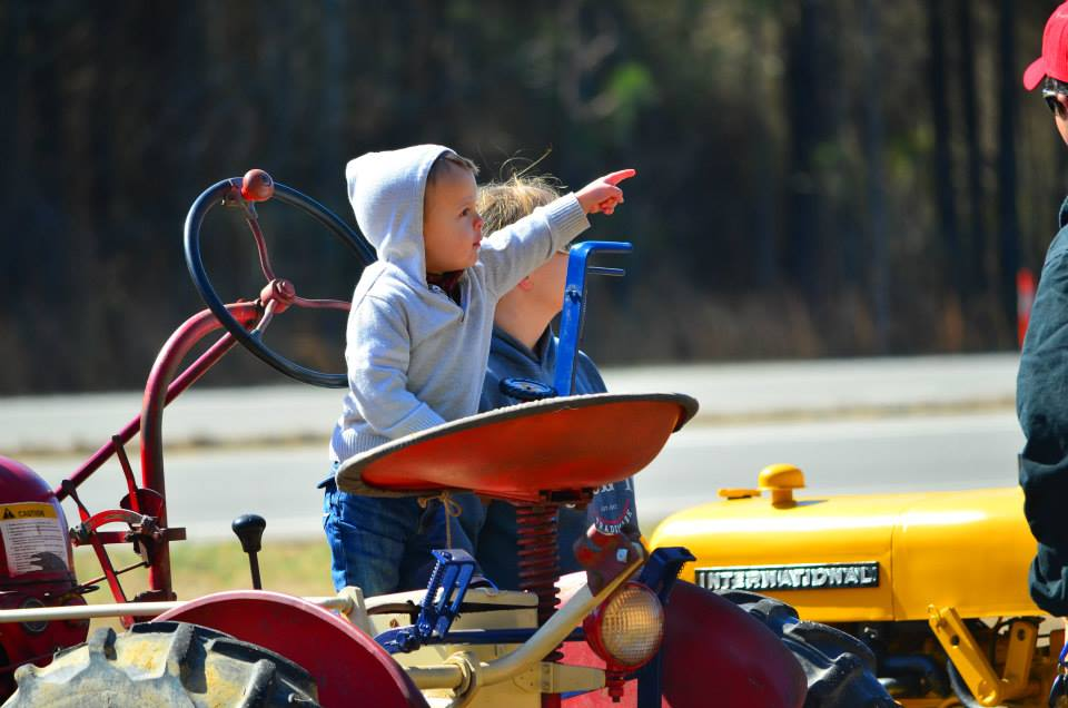Child on tractor pointing