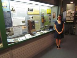 Intern standing next to exhibit