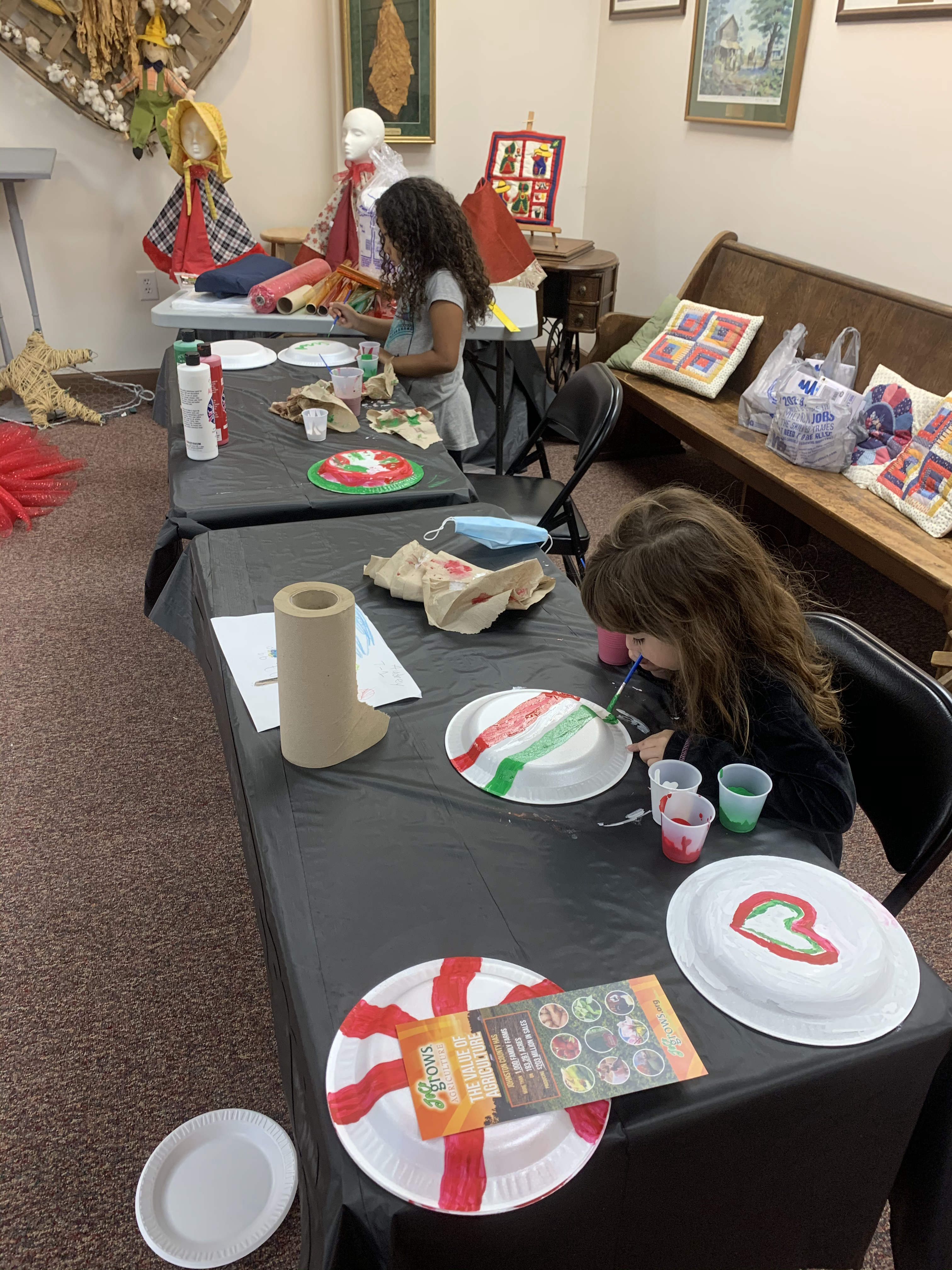 Two little girls painting the items that were part of the candy decorations for the gingerbread hous